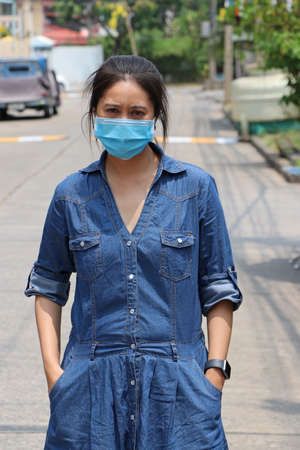 Masked Asian woman prevent germs and wear denim skirt dress. Tiny Particle or virus corona or Covid 19 protection. Concept of Combating illness. Foto de archivo