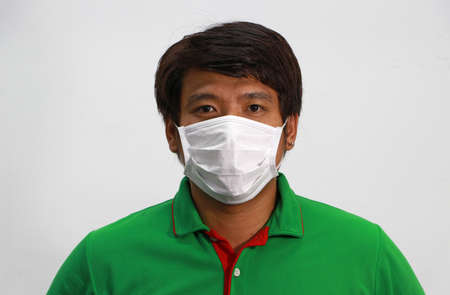 Masked Asian man prevent germs and wear green shirt. Tiny Particle or virus corona or Covid 19 protection. Concept of Combating illness. Reklamní fotografie