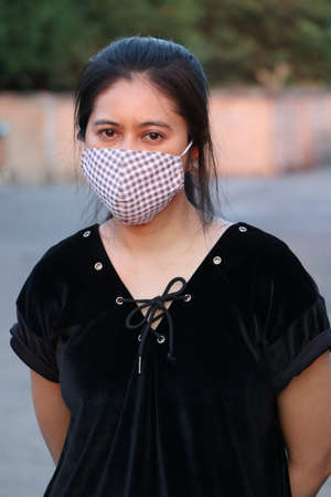 Masked Asian woman prevent germs and wear black clothing. Tiny Particle or virus corona or Covid 19 protection. Concept of Combating illness.
