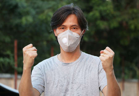 Masked Asian man prevent germs and wear grey shirt. Tiny Particle or virus corona or Covid 19 protection. Lift the fist up for meaning fighting or concept of Combating illness.