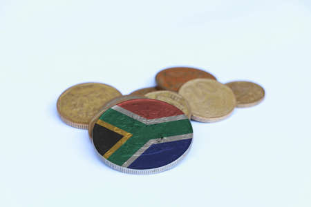 South Africa flag on the coin with heap of South African Rand money on the white background. Concept of finance or currency.