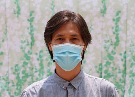 Masked Asian man prevent germs and wear blue shirt. Tiny Particle or virus corona or Covid 19 protection. Concept of Combating illness.