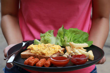 Breakfast in the black round plate on hand of woman wearing pink shirts. Bread with scrambled eggs and sausage, french fries with ketchup and chili sauce, lettuce and guava. Imagens
