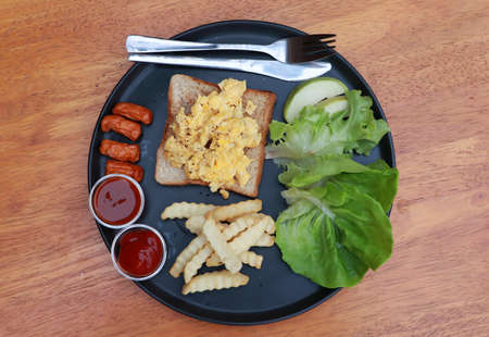 Breakfast in the black round plate on the wooden floor. Bread with scrambled eggs and sausage, french fries with ketchup and chili sauce, lettuce and guava. Imagens