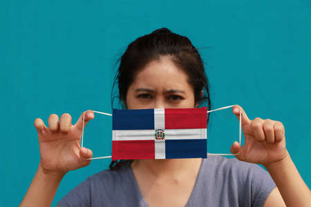 A woman with Dominican flag on hygienic mask in her hand and lifted up the front face on light blue color background. Tiny Particle or virus corona or Covid 19 protection. Concept of Combating illness.