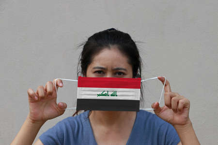 A woman with Iraq flag on hygienic mask in her hand and lifted up the front face on beige color background. Tiny Particle or virus corona or Covid 19 protection. Concept of Combating illness.