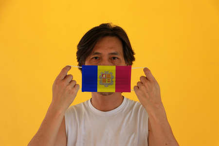 A man with Andorra flag on hygienic mask in her hand and lifted up the front face on yellow background. Tiny Particle or virus corona or Covid 19 protection. Concept of Combating illness.