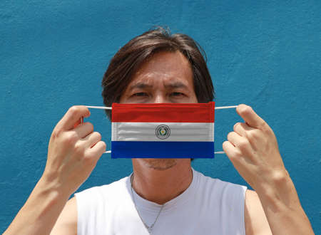 A man with Paraguay flag on hygienic mask in her hand and lifted up the front face on blue background. Tiny Particle or virus corona or Covid 19 protection. Concept of Combating illness.