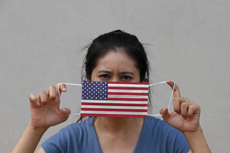 A woman with America flag on hygienic mask in her hand and lifted up the front face on beige color background. Tiny Particle or virus corona or Covid 19 protection. Concept of Combating illness.