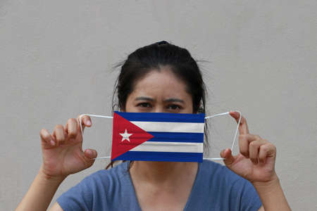 A woman with Cuba flag on hygienic mask in her hand and lifted up the front face on beige color background. Tiny Particle or virus corona or Covid 19 protection. Concept of Combating illness.