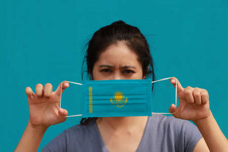 A woman with Kazakhstan flag on hygienic mask in her hand and lifted up the front face on light blue color background. Tiny Particle or virus corona or Covid 19 protection. Concept of Combating illness. Reklamní fotografie