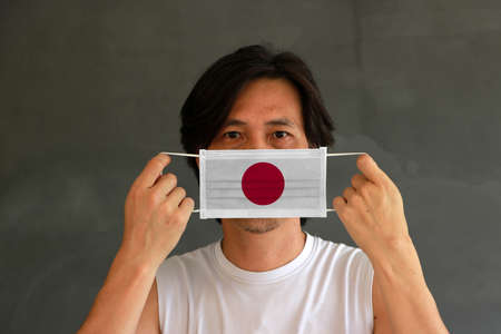 A man with Japan flag on hygienic mask in his hand and lifted up the front face on dark grey background. Tiny Particle or virus corona or Covid 19 protection. Concept of Combating illness.