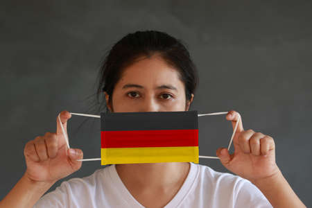 A woman in white shirt with Germany flag on hygienic mask in her hand and lifted up the front face on dark grey background. Tiny Particle or virus corona or Covid 19 protection. Concept of Combating illness. Reklamní fotografie