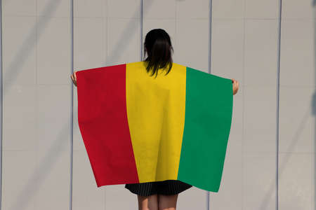 Woman is holding Guinea flag on her shoulder and turn back on grey background.