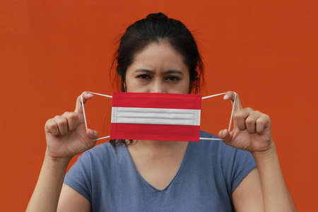 A woman with Austria flag on hygienic mask in her hand and lifted up the front face on orange color background. Tiny Particle or virus corona or Covid 19 protection. Concept of Combating illness.