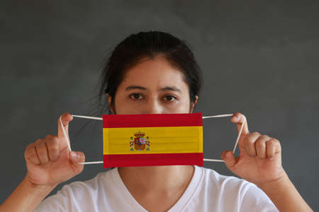 A woman in white shirt with Spain flag on hygienic mask in her hand and lifted up the front face on dark grey background. Tiny Particle or virus corona or Covid 19 protection. Concept of Combating illness.