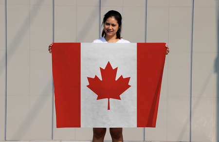pretty lady is holding Canada flag in her hands on grey background. Reklamní fotografie