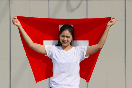 pretty lady is holding Switzerland Island flag in her hands and raising to the end of the arm at the back on grey background.