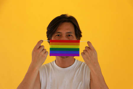 A man with LGBT+ flag on hygienic mask in his hand and lifted up the front face on yellow background. Tiny Particle or virus corona or Covid 19 protection. Concept of Combating illness. Reklamní fotografie