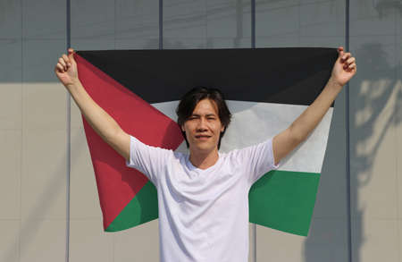 The man is holding Palestine flag in his hands and raising to the end of the arm at the back on grey background.