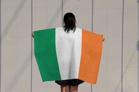 Woman is holding Ireland flag on her shoulder and turn back on grey background.