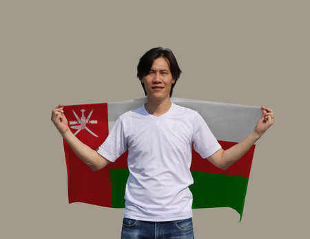 The man is holding Oman fabric flag on his shoulder on grey background. Reklamní fotografie