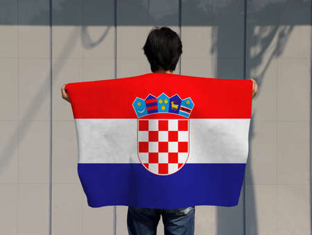 The man is holding Croatia flag on his shoulder and turn back on grey background.