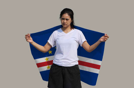 Woman is holding Cape verde fabric flag on her shoulder on grey background.