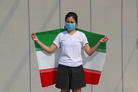 Masked woman prevent germs and holding Iran fabric flag on her shoulder on grey background. Tiny Particle or virus corona or Covid 19 protection. Imagens