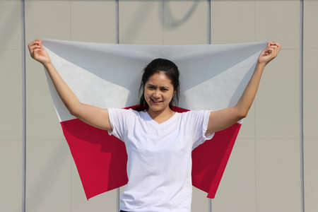 pretty lady is holding Poland flag in her hands and raising to the end of the arm at the back on grey background.