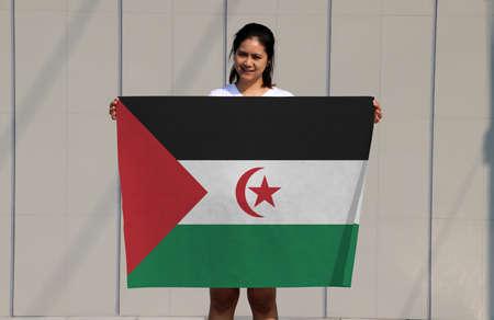 pretty lady is holding Sahrawi Arab flag in her hands on grey background. Reklamní fotografie