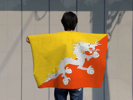 The man is holding Bhutan flag on his shoulder and turn back on grey background.