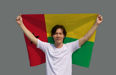 The man is holding Guinea Bissau flag in his hands and raising to the end of the arm at the back on grey background.
