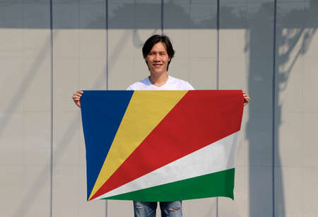 The man is holding Seychelles flag in his hands on grey background.
