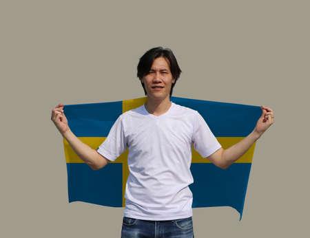 The man is holding Sweden flag on his shoulder on grey background.