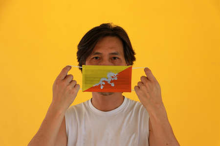 A man with Bhutan flag on hygienic mask in his hand and lifted up the front face on yellow background. Tiny Particle or virus corona or Covid 19 protection. Concept of Combating illness. Imagens