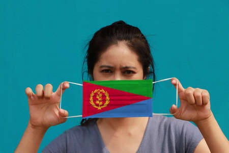 A woman with Eritrea flag on hygienic mask in her hand and lifted up the front face on light blue color background. Tiny Particle or virus corona or Covid 19 protection. Concept of Combating illness. Imagens