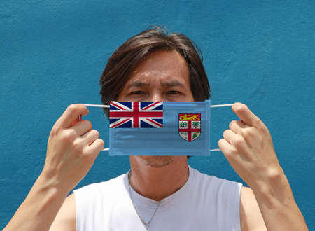A man with Fiji flag on hygienic mask in his hand and lifted up the front face on blue background. Tiny Particle or virus corona or Covid 19 protection. Concept of Combating illness.
