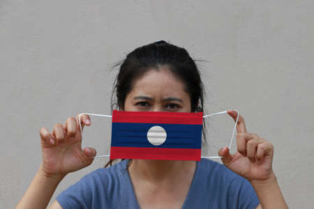 A woman with Laos flag on hygienic mask in her hand and lifted up the front face on beige color background. Tiny Particle or virus corona or Covid 19 protection. Concept of Combating illness.