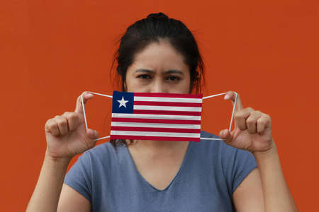 A woman with Liberia flag on hygienic mask in her hand and lifted up the front face on orange color background. Tiny Particle or virus corona or Covid 19 protection. Concept of Combating illness.