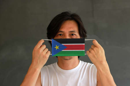 A man with South Sudan flag on hygienic mask in his hand and lifted up the front face on dark grey background. Tiny Particle or virus corona or Covid 19 protection. Concept of Combating illness. Imagens