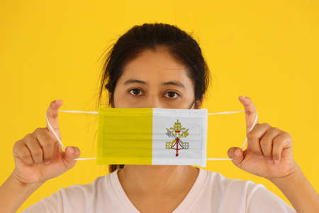 A woman in white shirt with Vatican City flag on hygienic mask in her hand and lifted up the front face on yellow background. Tiny Particle or virus corona or Covid 19 protection. Concept of Combating illness.