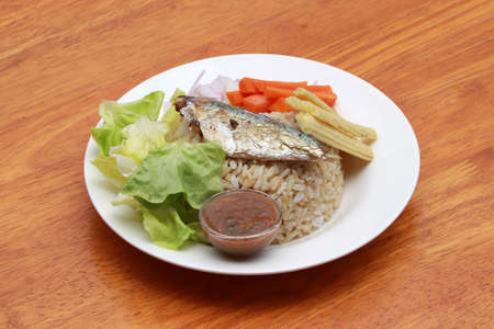 Breakfast in the white round plate on wooden floor. Fried mackerel and Rice with Spicy Shrimp Paste Dip and vegetable, Chinese cabbage, baby corn, carrots and sliced onions.
