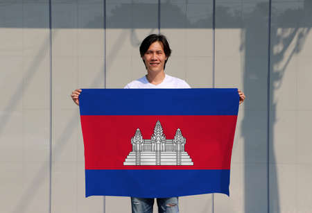 The man is holding Cambodia flag in his hands on grey background. Imagens