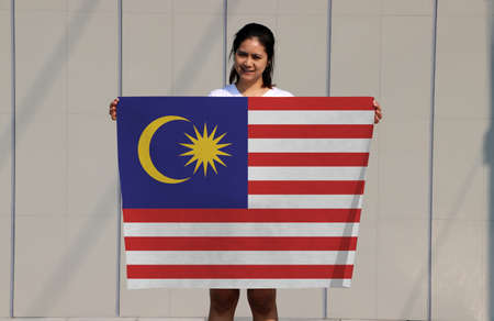 pretty lady is holding Malaysia flag in her hands on grey background. Reklamní fotografie
