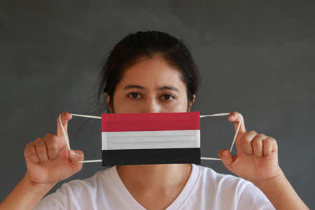 A woman in white shirt with Yemen flag on hygienic mask in her hand and lifted up the front face on dark grey background. Tiny Particle or virus corona or Covid 19 protection. Concept of Combating illness.