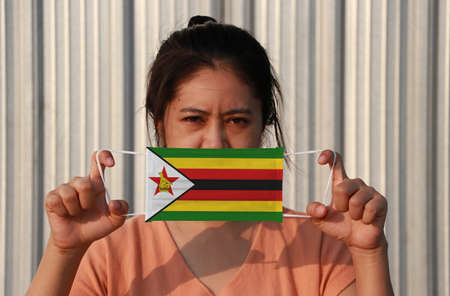 A woman with Zimbabwe flag on hygienic mask in her hand and lifted up the front face on grey background. Tiny Particle or virus corona or Covid 19 protection. Concept of Combating illness. Imagens
