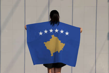 Woman is holding Kosovo flag on her shoulder and turn back on grey background.
