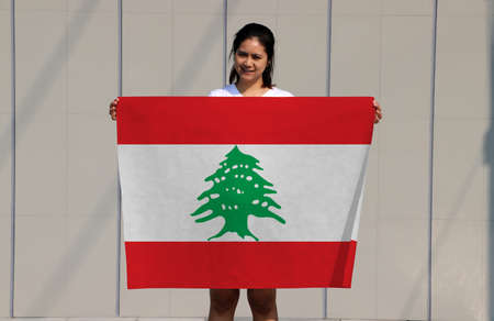 pretty lady is holding Lebanon flag in her hands on grey background.