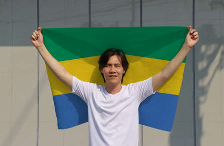 The man is holding Gabon flag in his hands and raising to the end of the arm at the back on grey background.